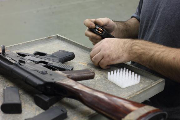 На столах кроме Калашниковых всё ещё лежат пистолеты